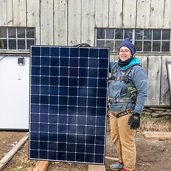 PV Squared employee Tia Fattaruso poses with  a solar panel ready to be installed on a barn in Shelburne, Massachusetts.