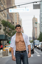 hot man walking in New York City with an open shirt