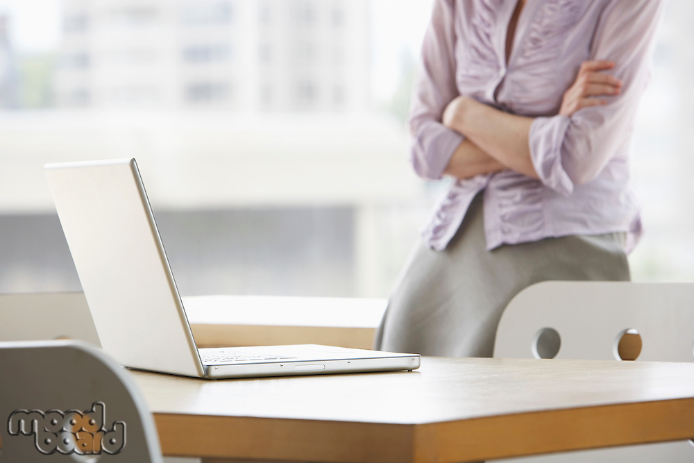Woman in office focus on laptop in foreground