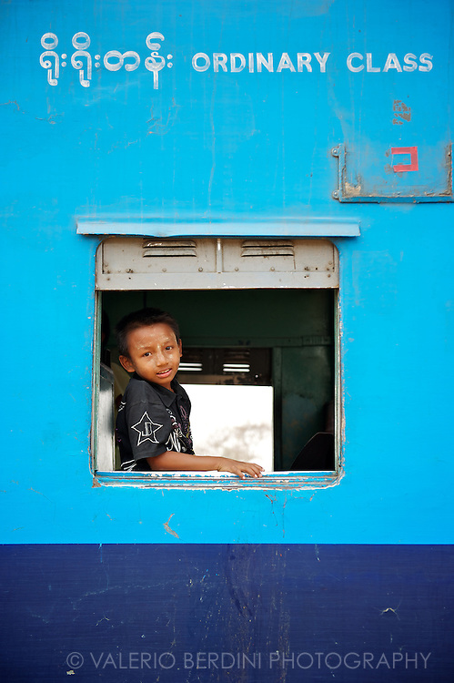 A boy glances from the window of one of the ordinary class coaches of a train.