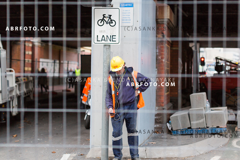 A construction worker with a hardhat and hi vis vest listens to music while playing on his phone whilst roadworks are being completed Melbourne Victoria Australia
