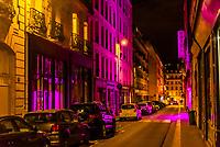 Magenta neon light illuminates the street at night, Rue Amelie, Paris, France.