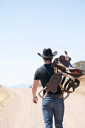 cowboy carrying a saddle over his shoulder outdoors