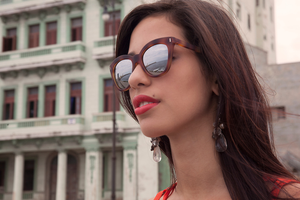 Young women looking at the sea in the Laecon Avenue, with the ocean reflected on her sunglasses.