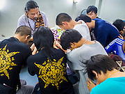 "07 MARCH 2015 - NAKHON CHAI SI, NAKHON PATHOM, THAILAND:  People pray to a tattoo master before he gave one of them a tattoo at the Wat Bang Phra tattoo festival. Wat Bang Phra is the best known ""Sak Yant"" tattoo temple in Thailand. It's located in Nakhon Pathom province, about 40 miles from Bangkok. The tattoos are given with hollow stainless steel needles and are thought to possess magical powers of protection. The tattoos, which are given by Buddhist monks, are popular with soldiers, policeman and gangsters, people who generally live in harm's way. The tattoo must be activated to remain powerful and the annual Wai Khru Ceremony (tattoo festival) at the temple draws thousands of devotees who come to the temple to activate or renew the tattoos. People go into trance like states and then assume the personality of their tattoo, so people with tiger tattoos assume the personality of a tiger, people with monkey tattoos take on the personality of a monkey and so on. In recent years the tattoo festival has become popular with tourists who make the trip to Nakorn Pathom province to see a side of ""exotic"" Thailand.  PHOTO BY JACK KURTZ"