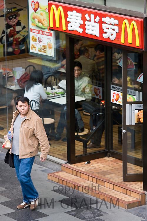 Chinese man leaves McDonalds fastfood restaurant on Nanjing Road, Shanghai, China