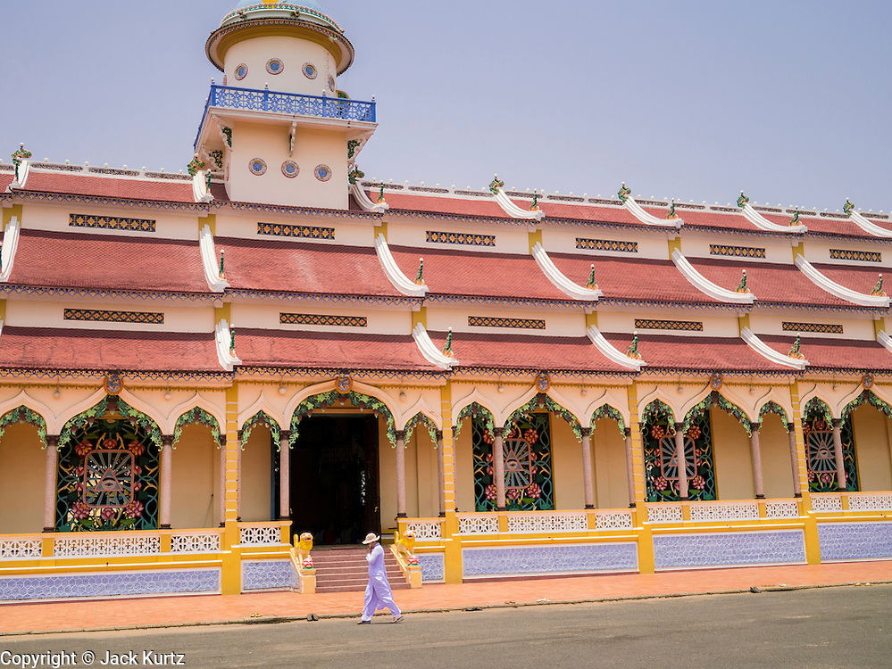 "29 MARCH 2012 - TAY NINH, VIETNAM:   A Cao Dai adherent walks past the main hall on the Cao Dai Holy See in Tay Ninh, Vietnam. Cao Dai (also Caodaiism) is a syncretistic, monotheistic religion, officially established in the city of Tây Ninh, southern Vietnam in 1926. Cao means ""high"" and ""Dai"" means ""dais"" (as in a platform or altar raised above the surrounding level to give prominence to the person on it). Estimates of Cao Dai adherents in Vietnam vary, but most sources give two to three million, but there may be up to six million. An additional 30,000 Vietnamese exiles, in the United States, Europe, and Australia are Cao Dai followers. During the Vietnam's wars from 1945-1975, members of Cao Dai were active in political and military struggles, both against French colonial forces and Prime Minister Ngo Dinh Diem of South Vietnam. Their opposition to the communist forces until 1975 was a factor in their repression after the fall of Saigon in 1975, when the incoming communist government proscribed the practice of Cao Dai. In 1997, the Cao Dai was granted legal recognition. Cao Dai's pantheon of saints includes such diverse figures as the Buddha, Confucius, Jesus Christ, Muhammad, Pericles, Julius Caesar, Joan of Arc, Victor Hugo, and the Chinese revolutionary leader Sun Yat-sen. These are honored at Cao Dai temples, along with ancestors.    PHOTO BY JACK KURTZ"
