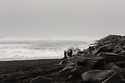 Waves being pushed in by an area of low pressure at Vik Beach, with a wave about to crash over a man at the waterline.