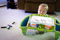JEROME A. POLLOS/Press..Gavin Scheel, 2, tips his art desk Friday to indicate he is done drawing with his markers.