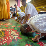 As monks recite prayers devotees bow before the Taoist idols.