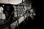 The city of Koundarà street scene, children look through a window.