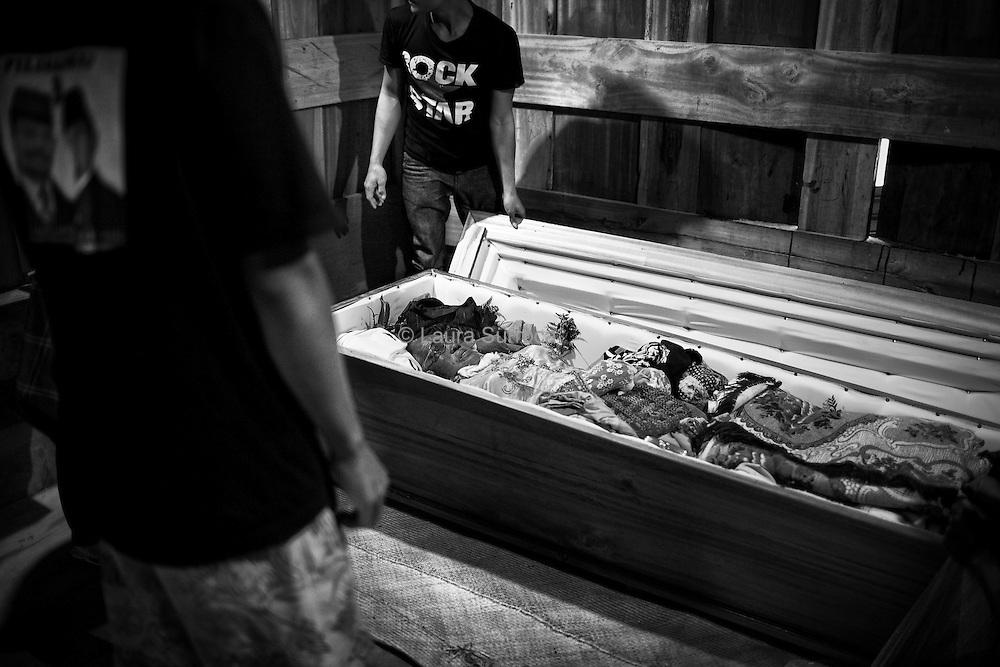 Tagari, 13 mars 2012. Le corps de Ruth est conservé dans du formol en attendant ses funérailles. La tradition toraja ancienne considère que tant que le corps du défunt est conservé à la maison, il n'est pas totalement mort. C'est la raison pour laquelle on trouve alimentation, boissons et cigarettes à proximité des cercueils. Lorsque les funérailles commencent, le défunt est alors définitivement considéré comme mort et peut commencer son voyage vers Puya.
