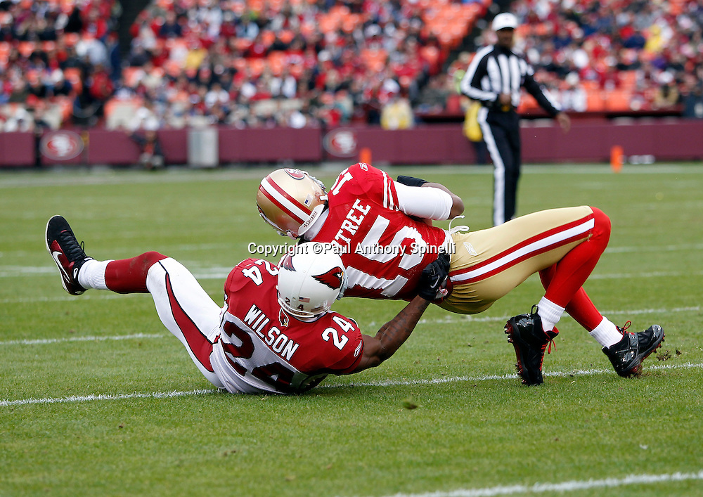 San Francisco 49ers wide receiver Michael Crabtree (15) catches a pass and gets tackled by Arizona Cardinals safety Adrian Wilson (24) during the NFL week 17 football game on Sunday, January 2, 2011 in San Francisco, California. The 49ers won the game 38-7. (©Paul Anthony Spinelli)