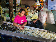 """12 JANUARY 2016 - BANGKOK, THAILAND: A vendor sorts bean sprouts in Khlong Toey Market in Bangkok. Khlong Toey (also called Khlong Toei) Market is one of the largest """"wet markets"""" in Thailand. The market is located in the midst of one of Bangkok's largest slum areas and close to the city's original deep water port. Thousands of people live in the neighboring slum area. Thousands more shop in the sprawling market for fresh fruits and vegetables as well meat, fish and poultry.         PHOTO BY JACK KURTZ"""