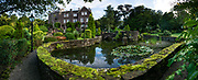 Pond. Comlongon Castle is a restored Medieval Scottish tower house dating from the late 1400s. Guests can stay in the attached Edwardian hotel, a baronial style mansion built 1900-02, set in 120 acres of manicured gardens, sweeping lawns, carp pond, lakes and woodlands, near Clarencefield and Dumfries, in southwest Scotland, United Kingdom, Europe. Originally built by the Murrays of Cockpool, Comlongon Castle remained in the Murray family until 1984. The castle is 50 feet square and stands 70 feet high, with walls over 4 meters thick, with impressive displays of weapons, armor and banners. This image was stitched from several overlapping photos.