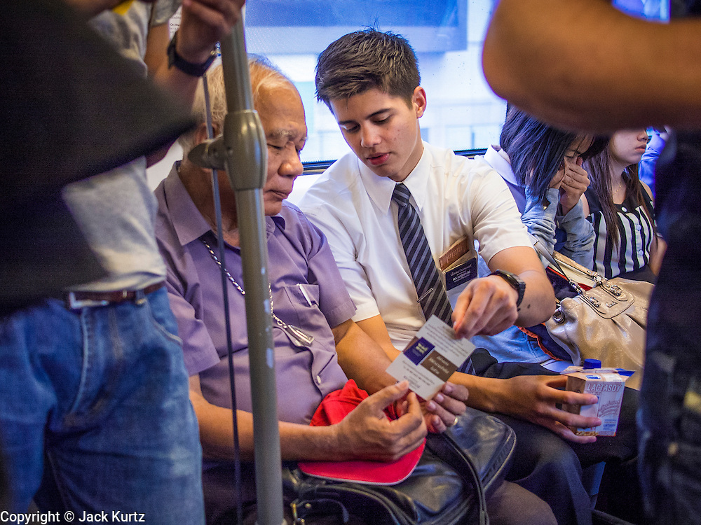 16 JULY 2013 - BANGKOK, THAILAND:   A missionary from the Church of Latter Day Saints, (LDS - Mormons) talks to a Thai Buddhist on the BTS Skytrain Sukhumvit line.     PHOTO BY JACK KURTZ
