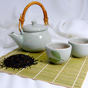 Green chinese teapot with tea cups and tea leaves ready to serve tea