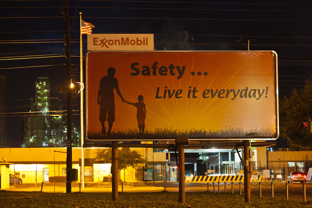"""Public relation sign at Exxon Mobile refinery in Baton Rouge, Louisiana located in the stretch between Baton Rouge and New Orleans along the river, is part of a large concentration of chemical and oil companies that was formerly referred to as the """"Petrochemical Corridor,"""" but now is know as """"Cancer Alley.""""  Many cases of cancer have occurred  in communities on both sides of the river though the Louisiana Tumor Registry claims the numbers are not higher then the national average. The record high levels of the Mississippi River in the spring of 2011 brought on by what some scientists clasify as climate change,  threaten the environment with the potential flooding of industrial complexes and nuclear facilities along the river."""