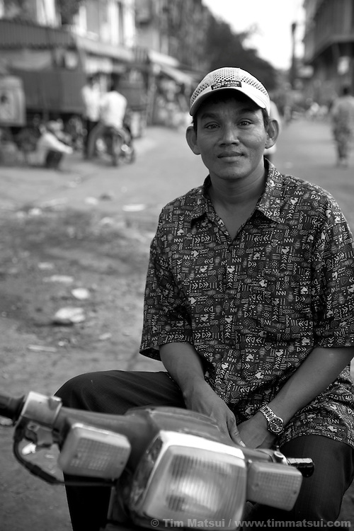 """Portrait of a moto taxi driver near a slum where the non governmental organization """"Acting for Women in Distressing Situations"""" (AFESIP), conducts outreach and provides services in Phnom Penh, Cambodia. The permanent structure at left, a decaying four story building known simply as 'The Building', was built in the 1960's as transitional housing and now hosts a shantytown where many of the city's poor live, including many prostitutes, and is believed to have the highest rate of HIV infection in the city. AFESIP hands out free condoms, instructs prostitutes on HIV prevention, and conducts outreach in case the prostitutes need medical services, choose to leave their profession, or can report on cases of sex trafficking. AFESIP offers housing, education, training, and counseling for women who are victims of sex trafficking, worked as prostitutes, or are escaping domestic violence. Founded by Somaly Mam, who herself was once a prostitute and victim of trafficking and domestic abuse, AFESIP has three facilities in Cambodia and works with other NGO's to provide long term care for the women."""