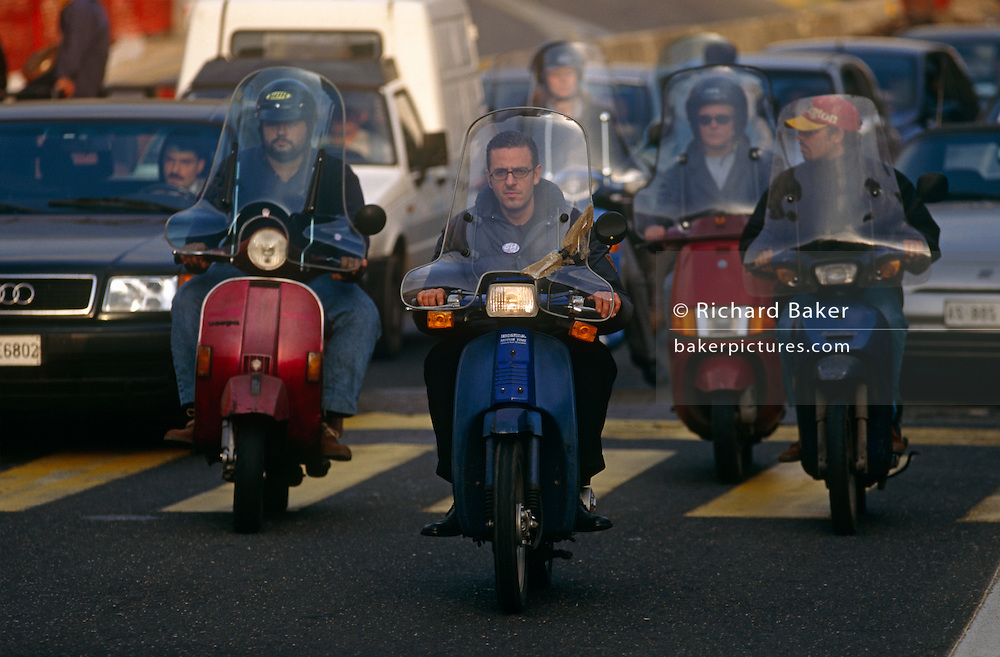 During Rome's chaotic rush hour, we see a fleet of scooters being ridden towards the viewer. Apparently chased by other commuters' cards at this busy road juntion, the traffic comes towards us as it passes over the yellow stripes of a pedestrian crossing who are probably huddled on the pavement awaiting a halt in the traffic flow. In the foreground is a young man without a helmet whose hands grip the handlebars and whose face looks at us as he rides hard ahead of his contemporaries, also on two-wheeled vehicles.