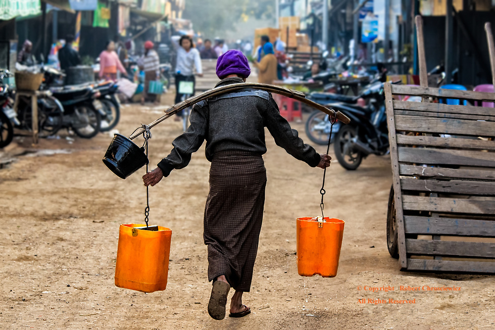 The Burden of Reality:  A man continues his solitary, life-long and unchallenged station in life; with the unrelenting burden of fate he finds himself at another morning market wearing a wooden yoke, hauling two yellow pails of water down a nearly deserted street, Nyaung U Myanmar.