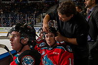 KELOWNA, BC - NOVEMBER 6:  Athletic therapist Scott Hoyer adjusts the helmet of Ethan Ernst #19 of the Kelowna Rockets on the bench against the Victoria Royals at Prospera Place on November 6, 2019 in Kelowna, Canada. (Photo by Marissa Baecker/Shoot the Breeze)