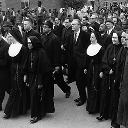 Responding tot he spirit of Vatican II, to rethink their life styles and update their communities, many nuns moved into active participation in the civil rights movement throughout the nation.  Though their actions developed conflict between them and the Church hiearchy, the commitment formed benefitted all concerned and brought an involvement which shattered the cloistered image of the past.  Typical of this are these nuns in the vanguad of a protest march in Selma, Alabama, March, 1965, led by the late Martin Luther King, Jr.