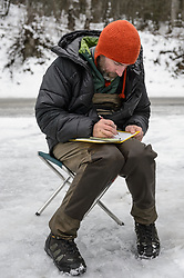 Steve Lewis, Raptor Management Coordinator, U.S. Fish & Wildlife Service, records information about a bald eagle (Haliaeetus leucocephalus) that was captured for a study being conducted by Rachel Wheat, a graduate student at the University of California Santa Cruz. Wheat is conducting a bald eagle migration study of eagles that visit the Chilkat River for her doctoral dissertation. She hopes to learn how closely eagles track salmon availability across time and space. The bald eagles are being tracked using solar-powered GPS satellite transmitters (also known as a PTT - platform transmitter terminal) that attach to the backs of the eagles using a lightweight harness. During late fall, bald eagles congregate along the Chilkat River to feed on salmon. This gathering of bald eagles in the Alaska Chilkat Bald Eagle Preserve is believed to be one of the largest gatherings of bald eagles in the world.