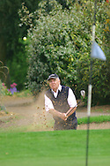 A golfer chips out of a bunker on the edge of the 8th green at Wellingborough Golf Club, Northamptonshire.