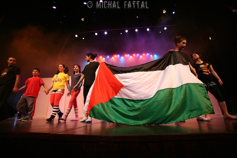 "The Palestinian Circus School members hold a Palestinian flag in the end of the show ""Circus behind the wall"" in Ramallah, November 20, 2009. The circus group was established in 2006, in order to give a new way of expression for Palestinians, and a new way to deliver the idea of resistance to the occupation. This performance shows the life of Palestinians behind the separation wall. Photo by Michal Fattal/Backyard"