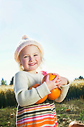 Portrait of a happy girl holding pumpkins