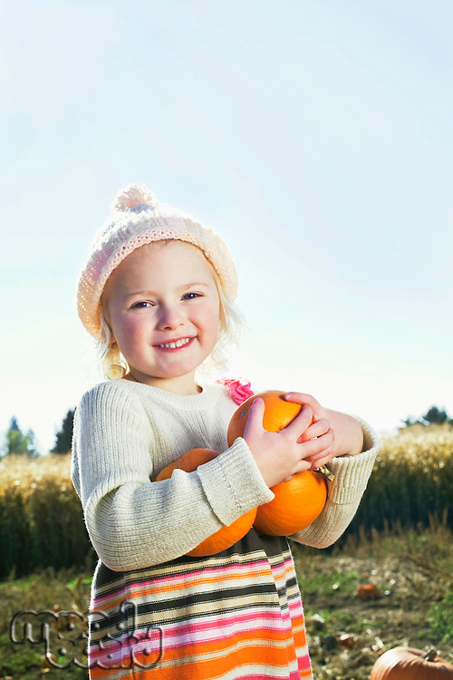 Portrait of a happy girl holding pumpkins