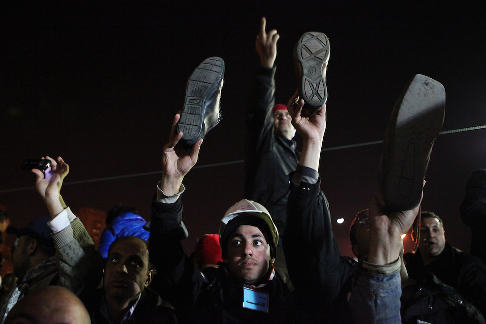 Pro-democracy protesters hold their shoes to the screen after Mubarak refused to step down in his third speech since protests began calling for his ouster.