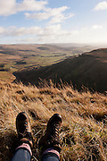 Hiking boots and legs in foreground with the view over the Moffat Hills on a clear day, Annandale Way, Devils Beeftub