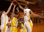 Riley senior Andy Harris (24) tries to shoot through Elkhart Memorial defenders Sean Stone (50) and Lamar Pittman (40) during Friday's game at North Side Gym in Elkhart. Jason Miller photo sports folder Feb. 27, 2004