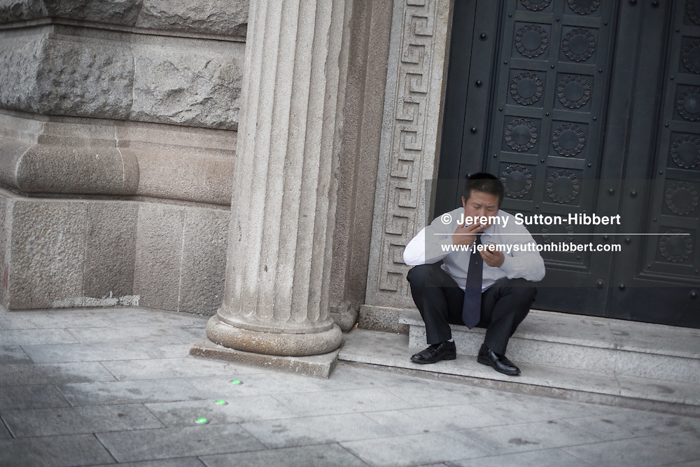 Salaryman, financial worker, male male smoking, in Shanghai, China, Wednesday 6th June 2012.