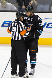 Feb 10, 2012; San Jose, CA, USA; San Jose Sharks center Joe Thornton (19) argues a call with NHL referee Tim Peel (20) during the first period against the Chicago Blackhawks at HP Pavilion. San Jose defeated Chicago 5-3. Mandatory Credit: Jason O. Watson-US PRESSWIRE