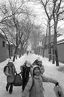 Beijing school children play in the snow on their way home in a hutong on a winter day.