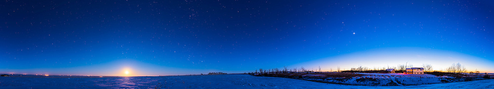 A 300&deg; panorama of the winter evening sky, January 12, 2017, with the Full &ldquo;Wolf&rdquo; Moon of mid-winter rising at left in the northeast, and Venus (brightest) and Mars (above) over in the southwest at right. Orion is rising in the east at centre, with Taurus above. The Big Dipper is at far left to the north. The remaining glow of twilight creates an arch of light in the southwest, while the rising Moon creates an arch of brighter sky at left. This was a very clear, transparent night but at -20&deg; C. Note the glitter path on the snow from the Moon. <br /> <br /> I shot this from home in southern Alberta, using the Nikon D750 and 24mm Sigma Art lens. This is a stitch of 14 segments with generous overlap, stitched in Adobe Camera Raw.