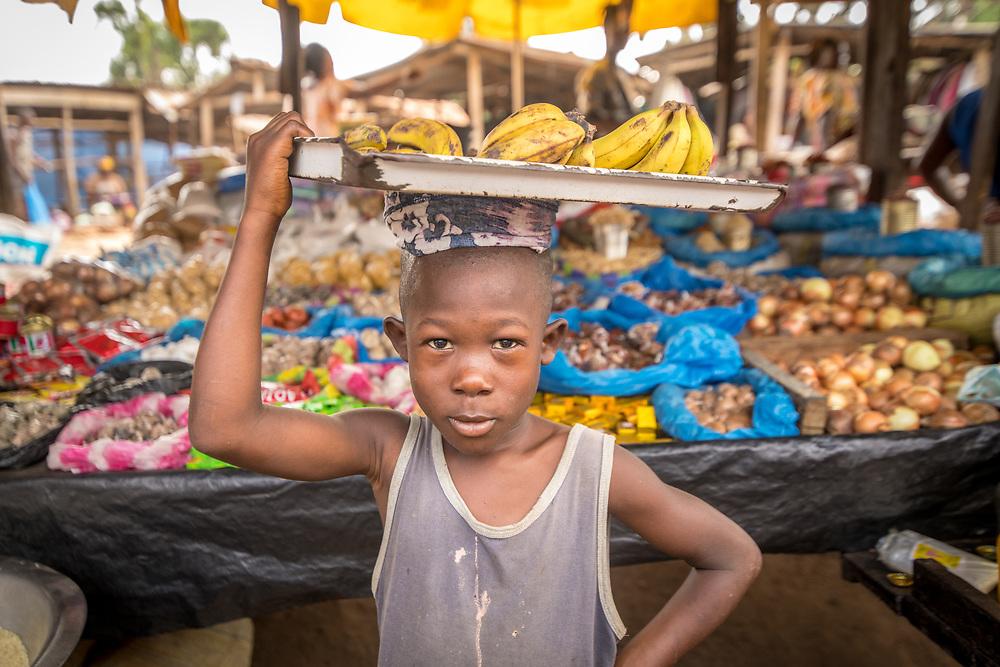 A boy carries bananas on his head through the market in Ganta, Liberia