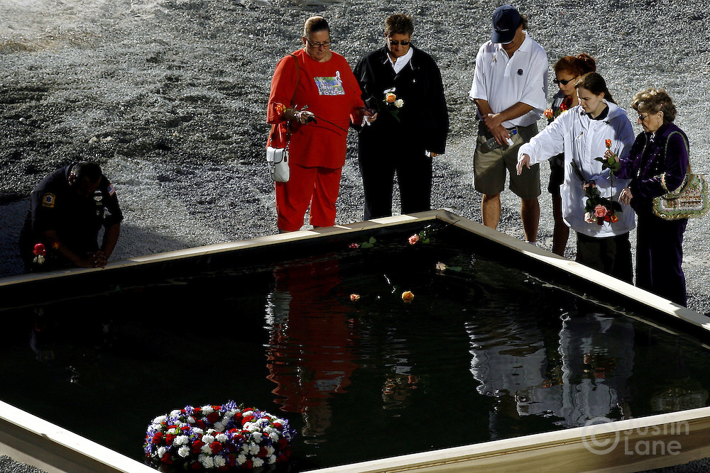 Family members throw flowers into one of two reflecting pools marking the locations of the World Trade Center towers during the September 11th commemoration ceremony in New York on Monday 11 September 2006. This year marks the five year anniversary of the attacks. ..