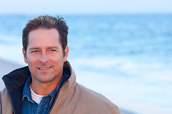 portrait of a handsome man outdoors wearing outerwear during the off season at the beach