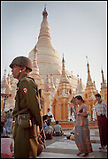 Burma, Thailand tab: Soldier, Rangoon, Shwedegon Pagoda. : A LAND OF WAR : A JOURNEY OF THE HEART : &quot; THIS IS A DANGEROUS COUNTRY,&quot; A BURMESE MAN SAYS, EXPLAINING THE SUDDEN APPEARANCE OF ARMED SOLDIERS AMONG WORSHIPERS AT SHWEDAGON PAGODA, RANGOON'S MOST CELEBRATED TEMPLE. THE CAPITAL WAS ESPECIALLY ON EDGE AFTER A BOMB BLAST KILLED THE DAUGHTER OF ONE OF THE NATION'S MILITARY RULERS. DR. CYNTHIA LATER WOUND UP ON A SHORT LIST OF RELIEF ORGANIZATIONS WHOM THE REGIME BLAMED FOR THE BLAST. ( 18 OF 19 )<br /> <br /> Dr. Cynthia Maung