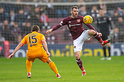 Michael Smith (#2) of Heart of Midlothian passes the ball past Steven Lawless (#15) of Livingston FC during the 4th round of the William Hill Scottish Cup match between Heart of Midlothian and Livingston at Tynecastle Stadium, Edinburgh, Scotland on 20 January 2019.