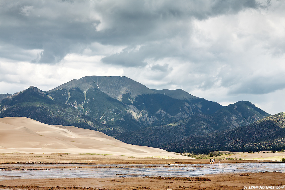 People cross Medano Creek and marvel at the sand dunes and Sangre de Cristo mountains beyond at Great Sand Dunes National Park, Colorado.