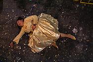 """Yenny Wilma Maraz, """"Marta La Alteña"""" derribada al piso se queja del dolor por una serie de golpes que recibio de su adversario durante su enfrentamiento de lucha libre. Las Cholitas usan el vestido tradicional de los Aymara para luchar en el cuadrilátero, en El Alto, Bolivia, el 26 de Febrero de 2012."""