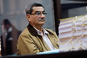 Former brigadier general Jose Mauricio Rodriguez Sanchez, contemplating files of evidence against him, having just been formally charged with the crime of genocide and acts against humanity towards  the Mayan people.  <br /> Court of Justice, Guatemala City, Guatemala, October 2011.