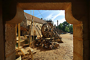 Lifting gear or squirrel cage with single drum and behind, the North Range or Logis Seigneurial, completed 2010, in the courtyard of the Chateau de Guedelon, a castle built since 1997 using only medieval materials and processes, photographed in 2017, in Treigny, Yonne, Burgundy, France. The Guedelon project was begun in 1997 by Michel Guyot, owner of the nearby Chateau de Saint-Fargeau, with architect Jacques Moulin. It is an educational and scientific project with the aim of understanding medieval building techniques and the chateau should be completed in the 2020s. Picture by Manuel Cohen