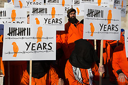 © Licensed to London News Pictures. 11/01/2014. London, UK. Activists from the London Guantanamo Campaign, wearing orange jumpsuits and black hoods, stage a protest in Trafalgar Square in London on 11 January 2014 to mark the 12th anniversary of the opening of the Guantanamo Bay prison camp and demand its closure. Orange suits are worn by protestors to remind of the suits worn by inmates of the US prison camp at Guantanamo Bay. Photo credit : Vickie Flores/LNP