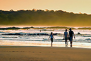 The famous waves of Playa Tamarindo, Costa Rica Are Reflected At Sunset As A Family Walks Next To The Pacific Ocean.